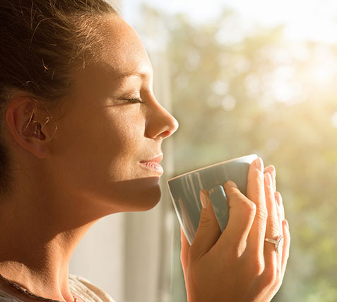 Content, peaceful woman, enjoying a cup of coffee